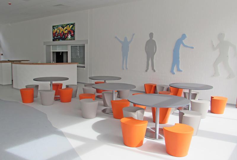 Pausenraum mit hellen Wänden und einer leuchtend-bunten Sitzecke