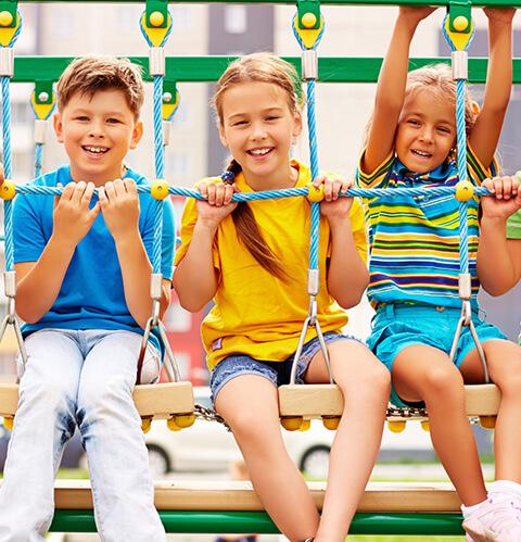 Drei Kinder sitzen auf einer Holzbrücke und lächeln in die Kamera – Architektur macht Schule