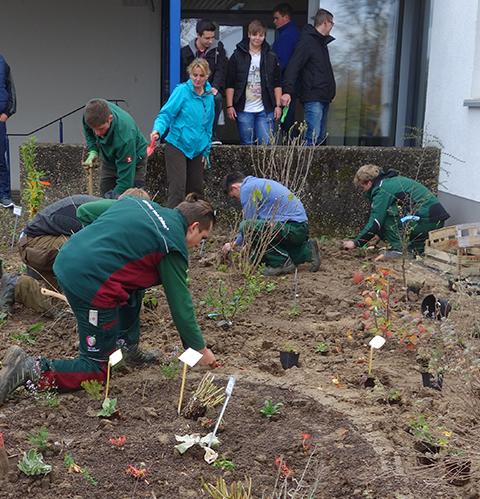 Gärtner bepflanzen ein Beet – Architektur macht Schule