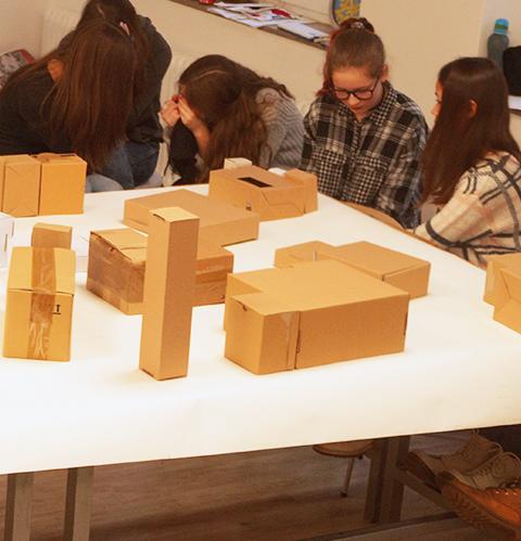 Schüler sitzen vor Kartons – Architektur macht Schule